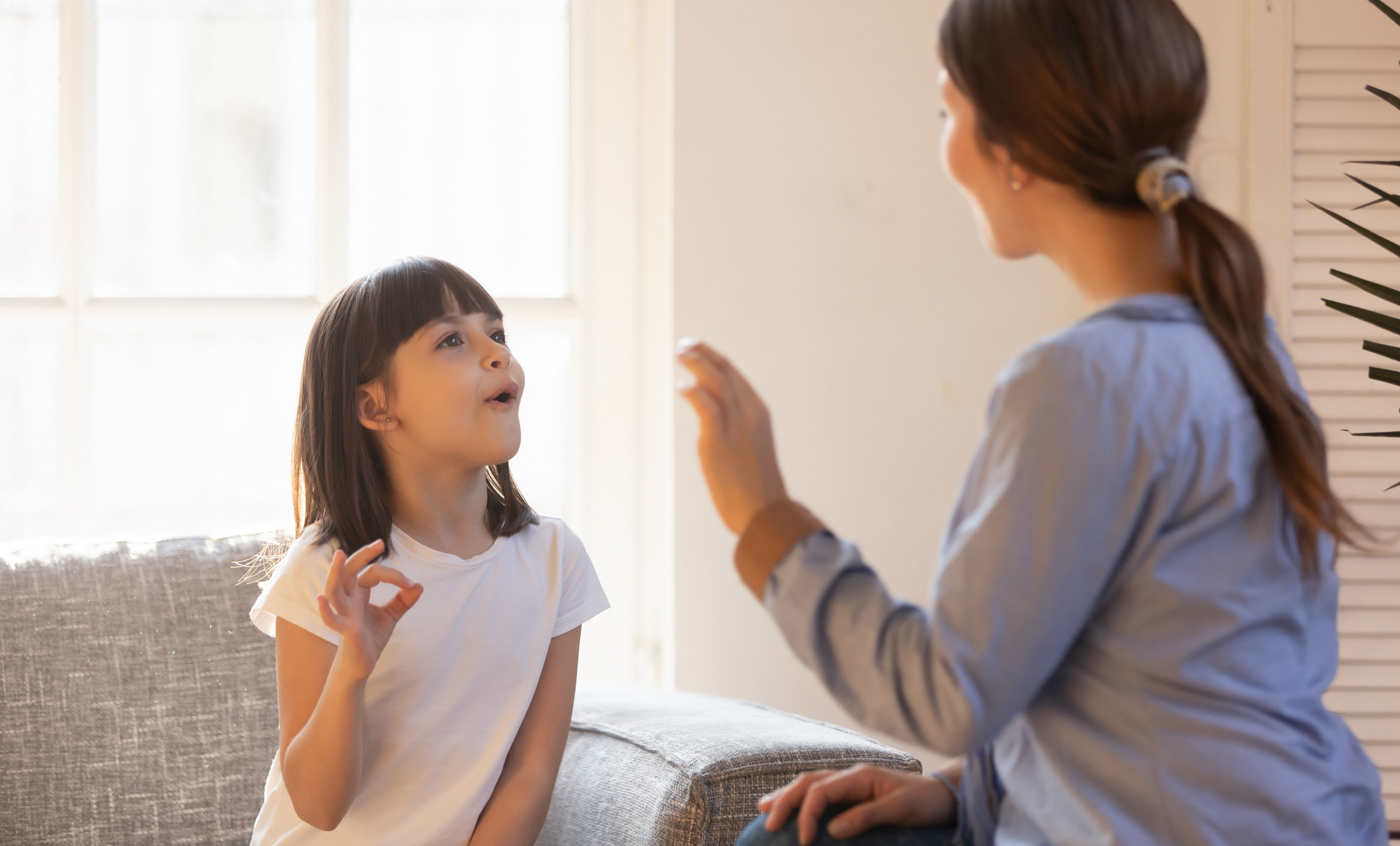 A woman teaching a young girl sign language.