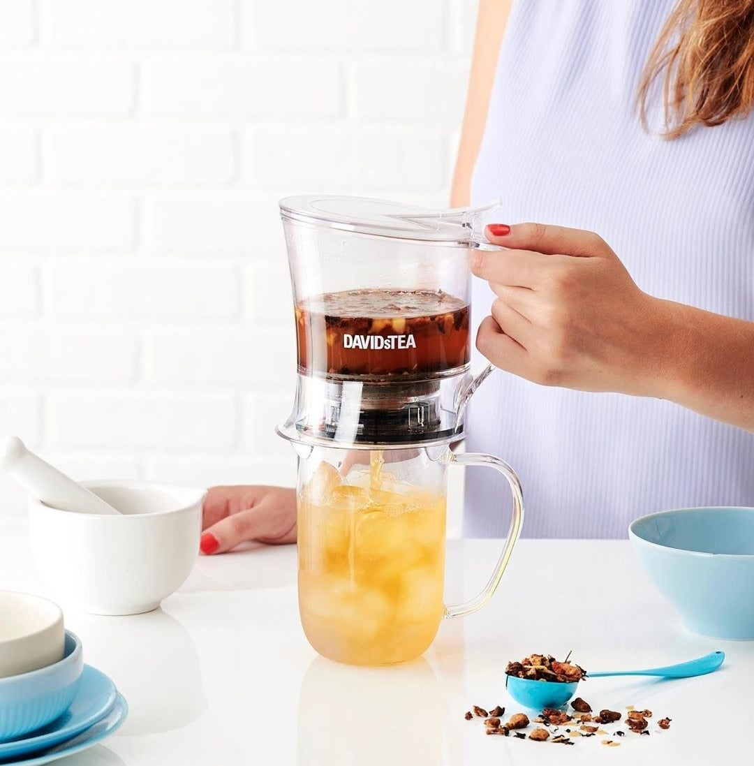 A person using the steeper to make themselves a cup of iced tea