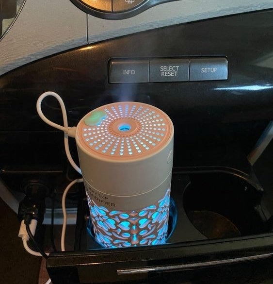 Reviewer using the mini car diffuser in their car's cup holder