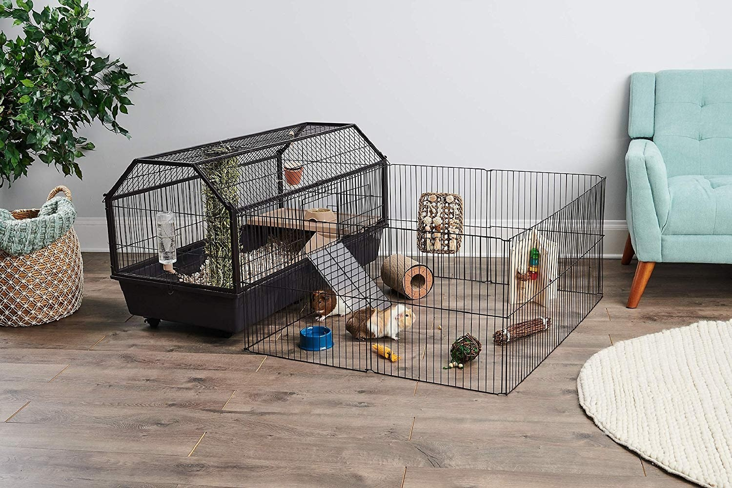 A large black gerbil cage with two levels and a ramp that runs down into an open caged area