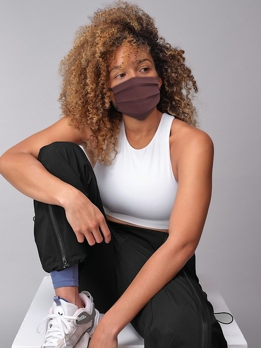 a model in athletic clothing wears a maroon mask