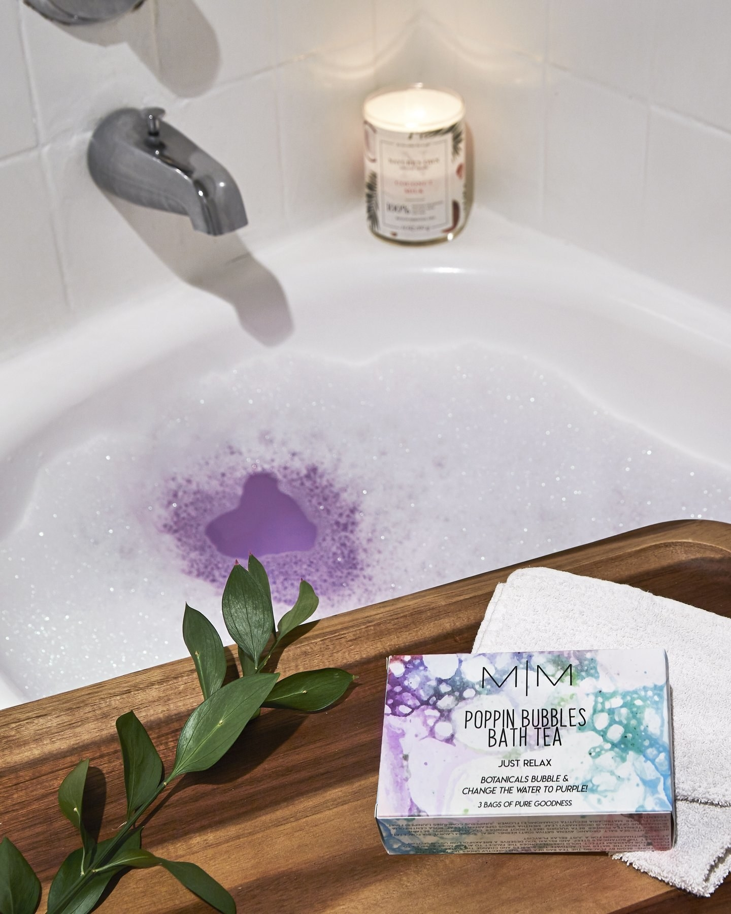 the box of bath tea on a wooden shelf above purple, foamy bath water