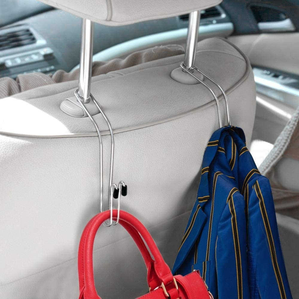 The silver hook hangers on a car seat, holding a purse and coat
