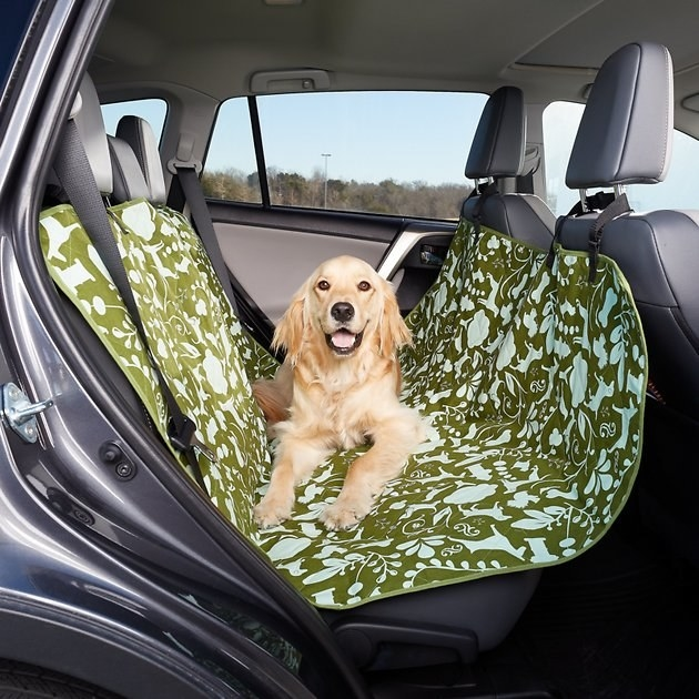 A patterned, thick mat with four straps hung on each car headrest and a dog laying in the center of it