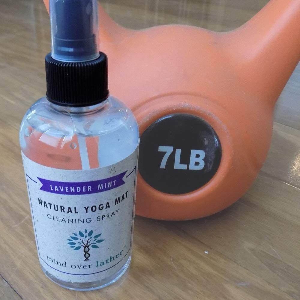 "clear bottle with black cap labeled ""lavender mint natural yoga mat cleaning spray"""