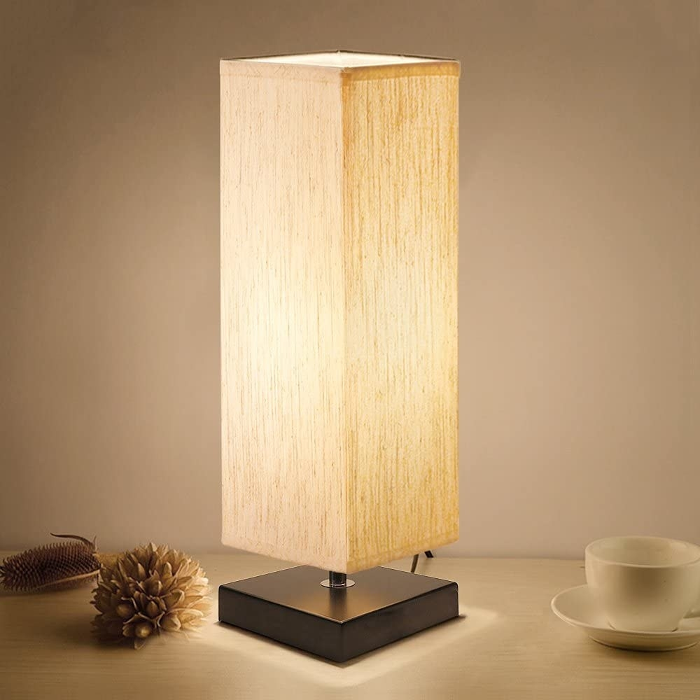 Lamp with square fabric shade in tan and dark brown wood base