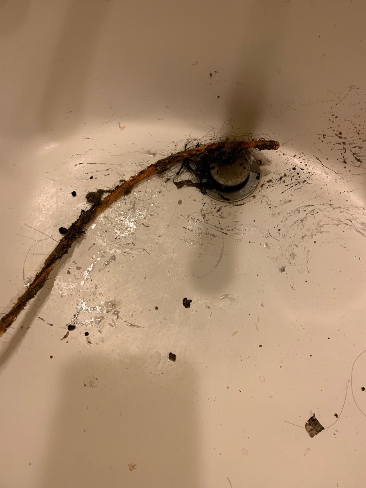 A review image of black goop and hair removed from the drain, in a tub