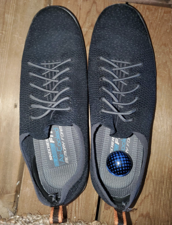 Reviewer photo of a pair of grey sneakers with a blue deodorizer ball in the right one