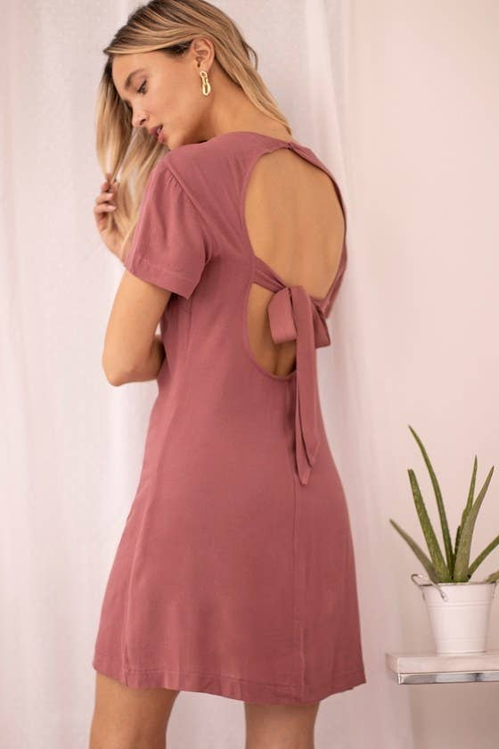 Model wearing shift dress in rose showing the circular open in the back with a tie through it