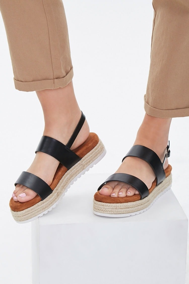 Model wearing shoes with a padded footbed in tan, black straps across the toes and top near ankle and adjustable ankle strap around the back of the foot