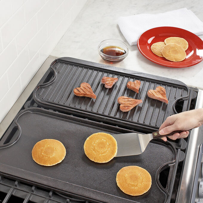 two of the cast-iron pans side by side to show case the flat side and the ribbed grill side