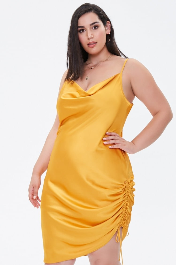 Model wearing yellow dress with side ruched self-tie drawstring and asymmetrical hem