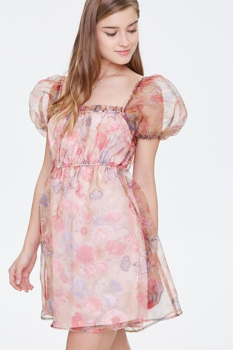 Model wearing the dress with a watercolor beige/pink floral print, square neckline, short puff sleeves, and elastic waist
