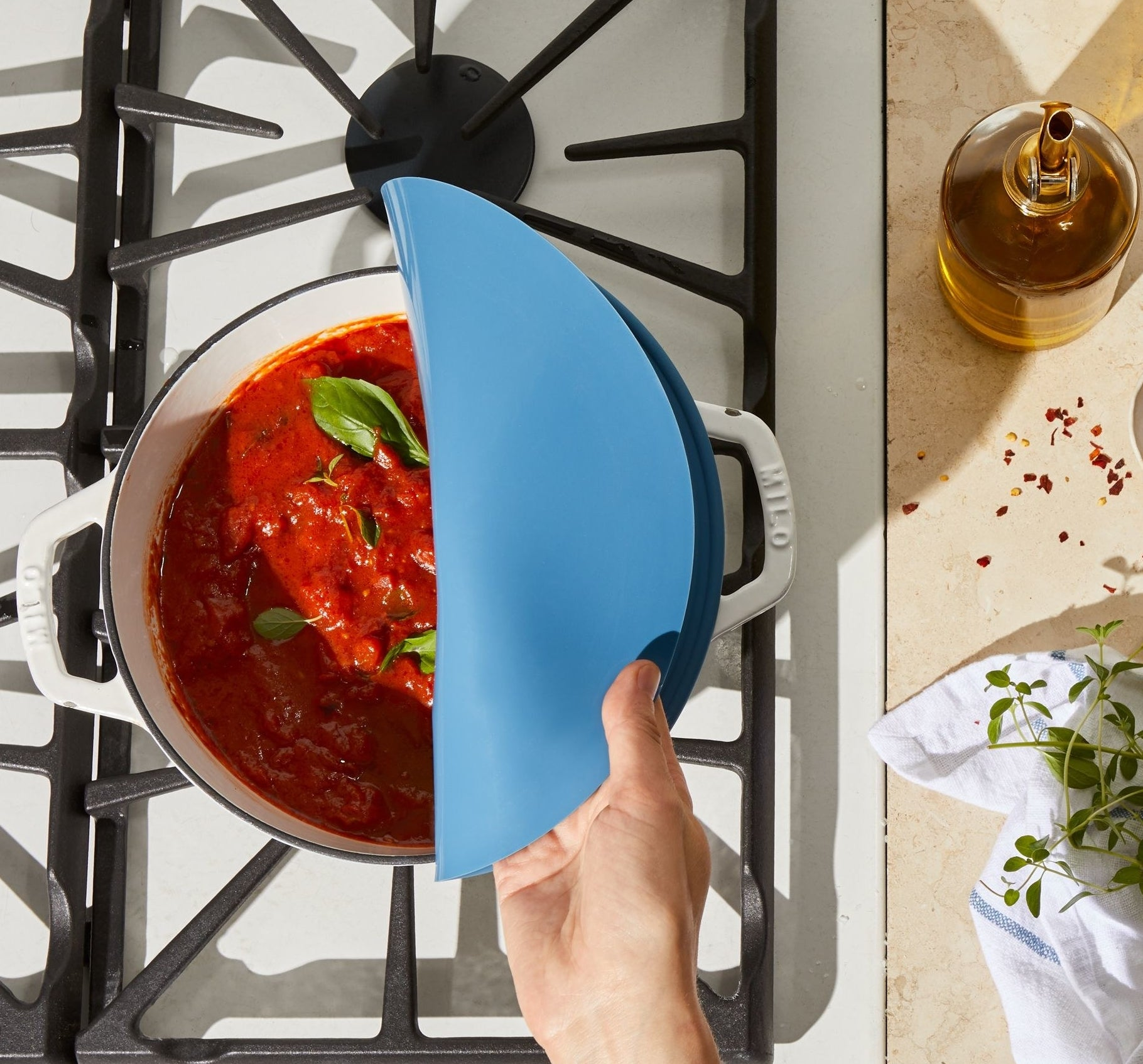 large blue lid on a dutch oven on the stove bent back to reveal tomato sauce