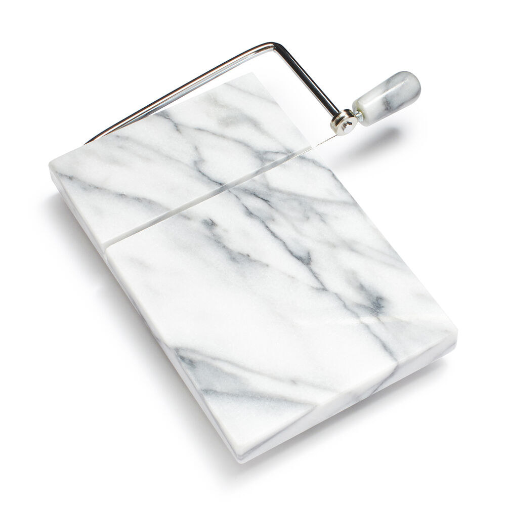 a white marble cutting board with a slicer attached