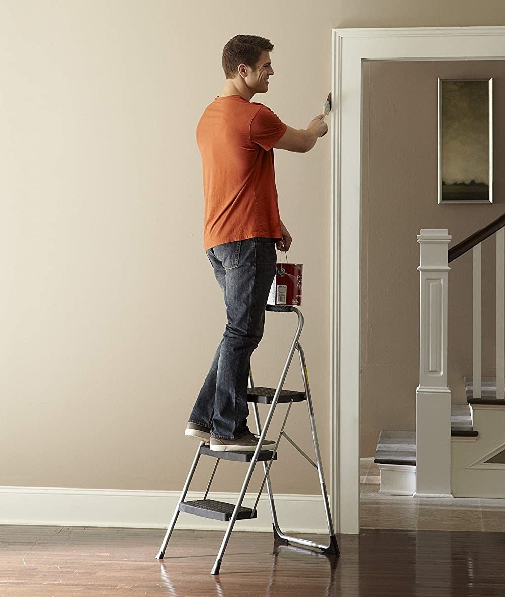 Model using the step stool to paint a high-up area of a wall