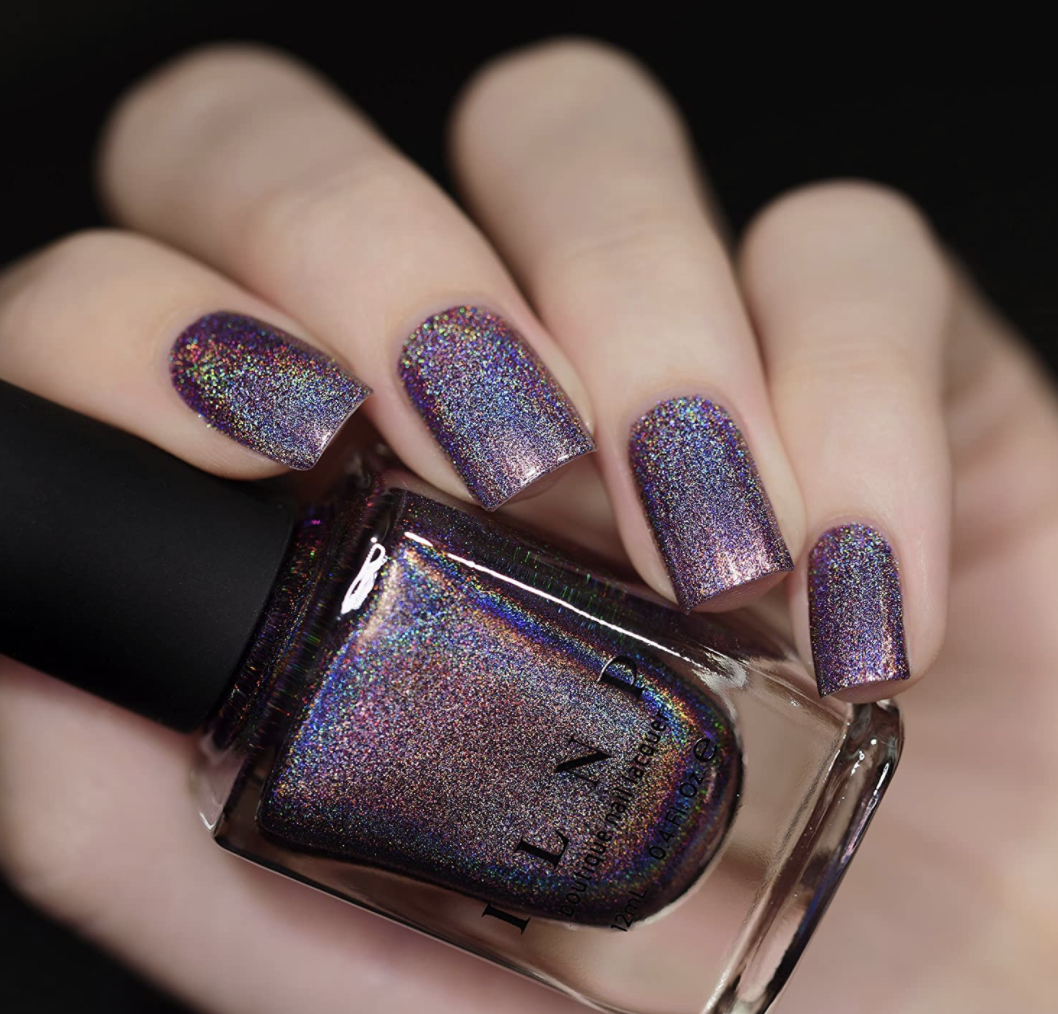 Model wears ILNP Charmed purple holographic nail polish on their hand
