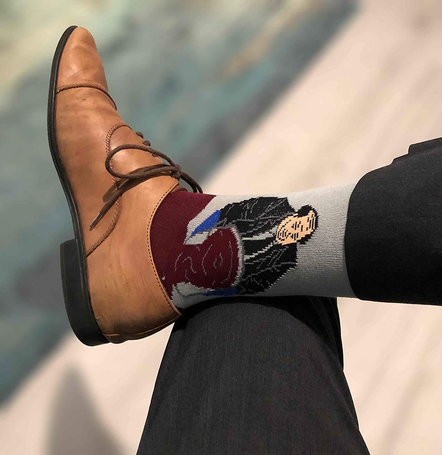 "A model wearing the socks peeking out of Oxford shoes. Kevin from ""The Office"" is on the ankle, and the red chili spilling out covers the foot"