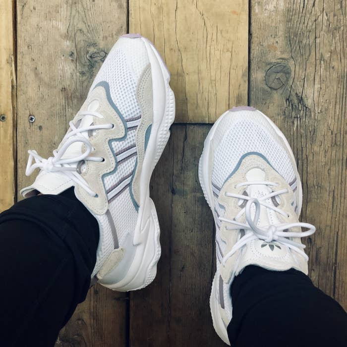 BuzzFeed editor showing the sneakers on feet in a white, tan, and lavender colorway