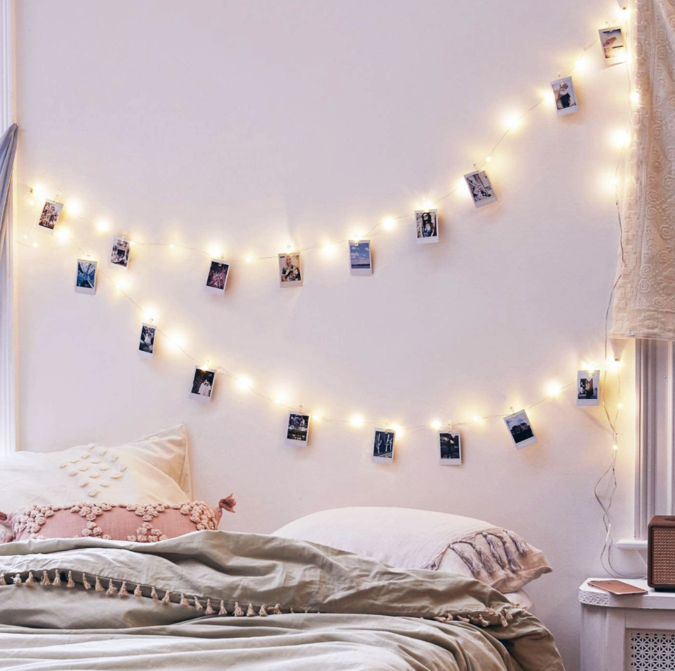 A set of photo clip string lights on a bedroom wall