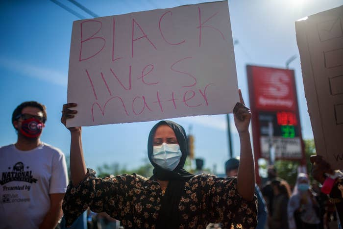 A woman wearing a facemask holds a sign during a protest in Minneapolis on May 29 over the death of George Floyd, a black man who died after a white police officer pinned him on the ground in a neck chokehold until he became unresponsive.