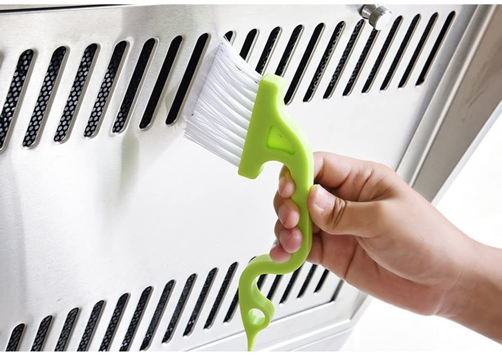 A person brushing out a vent with the gap-cleaning tool