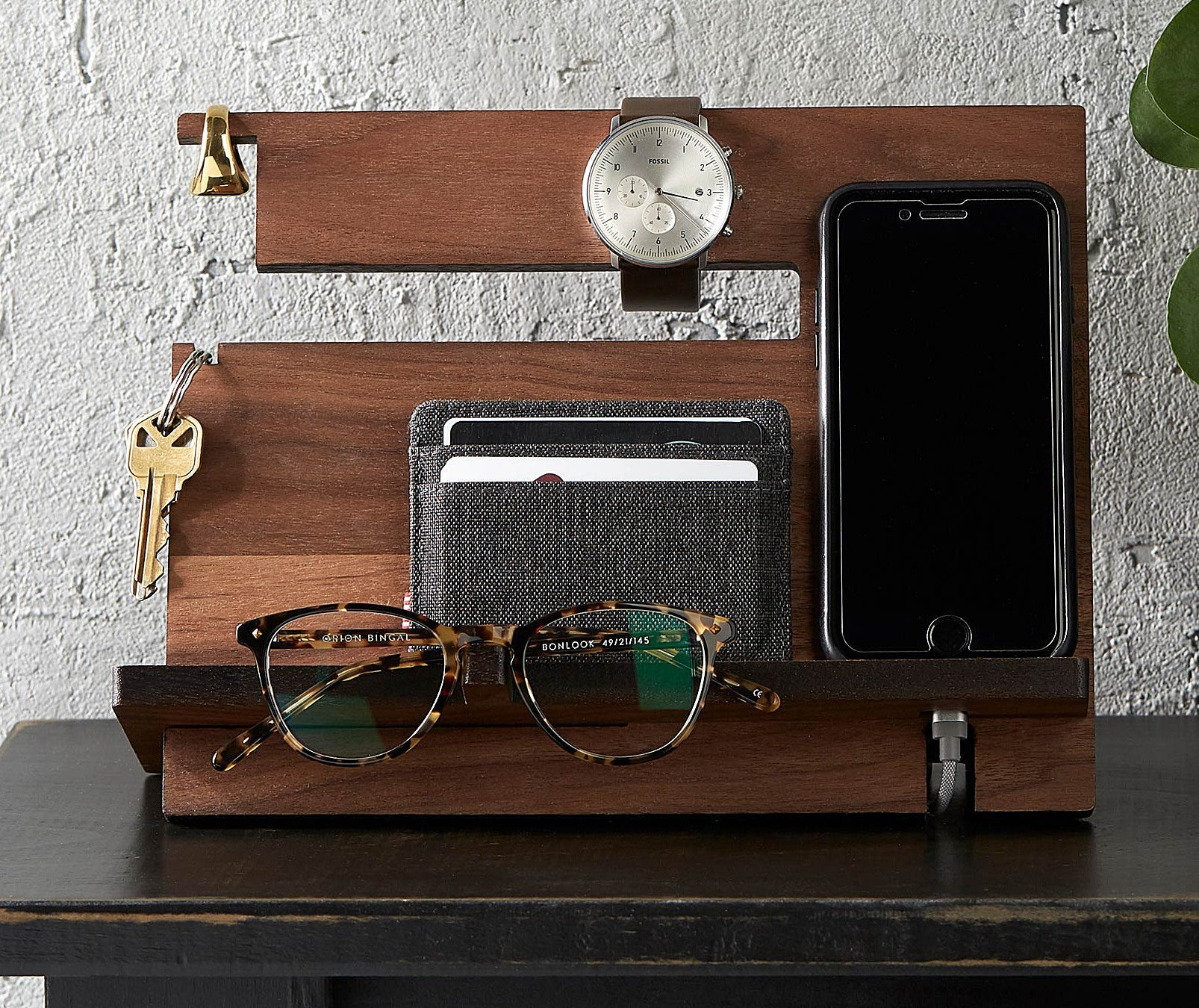 An upright wooden tray with a phone and wallet leaning against it