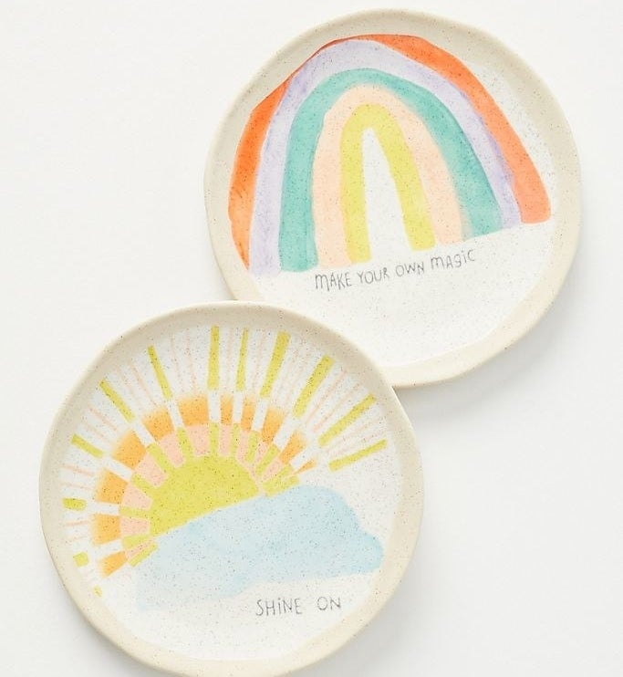 """A plate with a watercolor painted sun coming out of a cloud that says """"Shine On,"""" and another play with a painted rainbow that says """"Make Your Own Magic"""""""