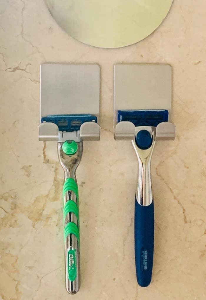 Two razors hanging on the razor holders