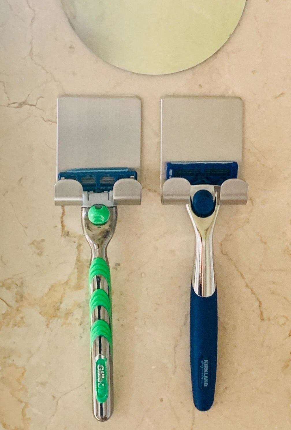 Two razors hanging on the silver razor holders