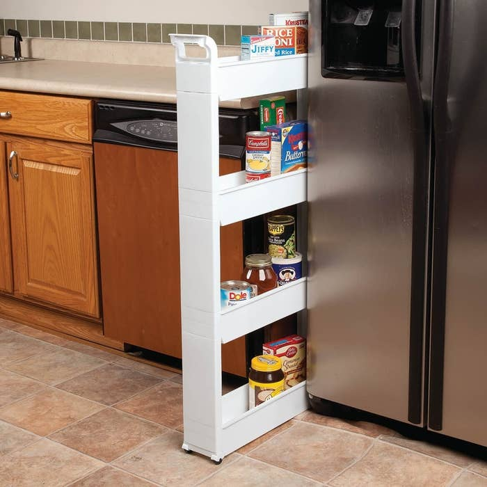 A thin shelf with four shelves rolling out from the gap between a kitchen counter and the fridge