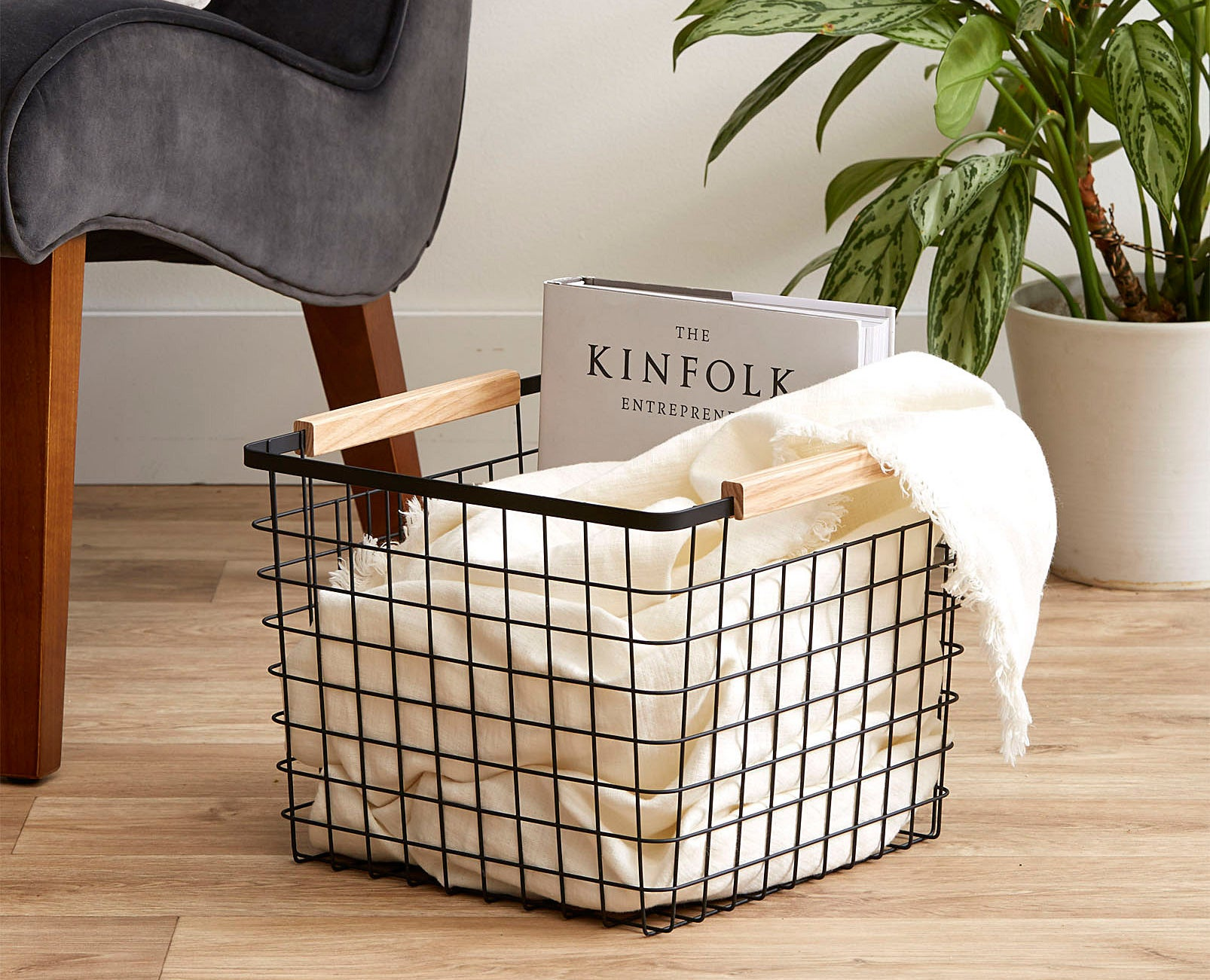 A metal wire basket with wooden handles There is a small blanket and a thick book inside
