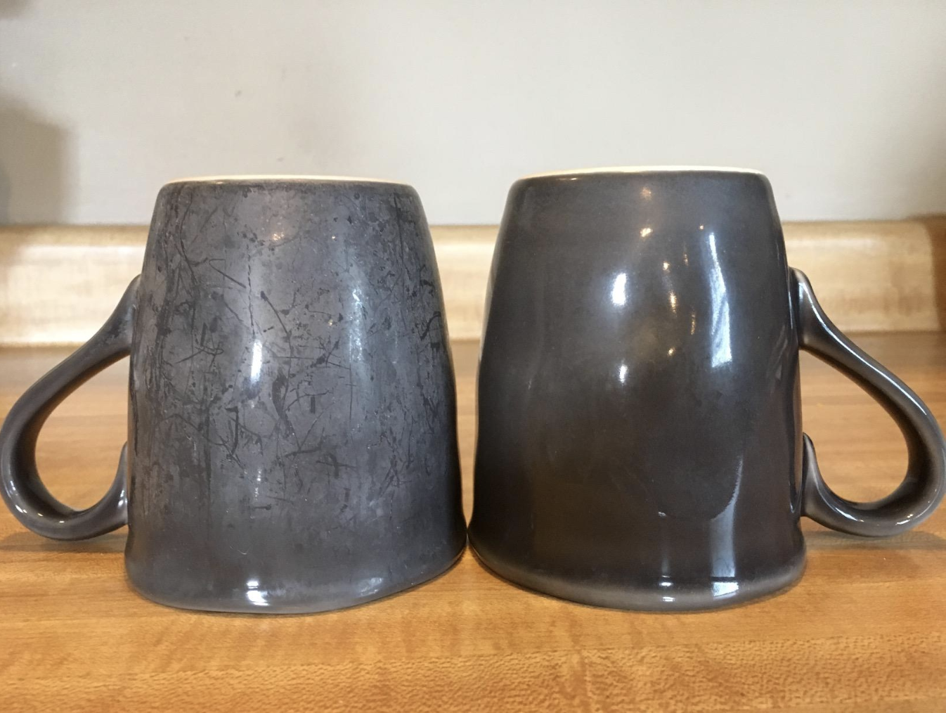 A hard water stained mug and a totally clean version of it sitting on a counter together