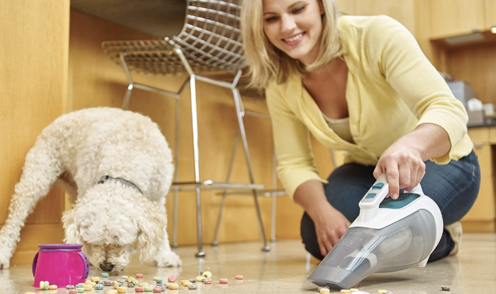 model holds white and gray handheld vacuum to clean up colorful cereal on floor