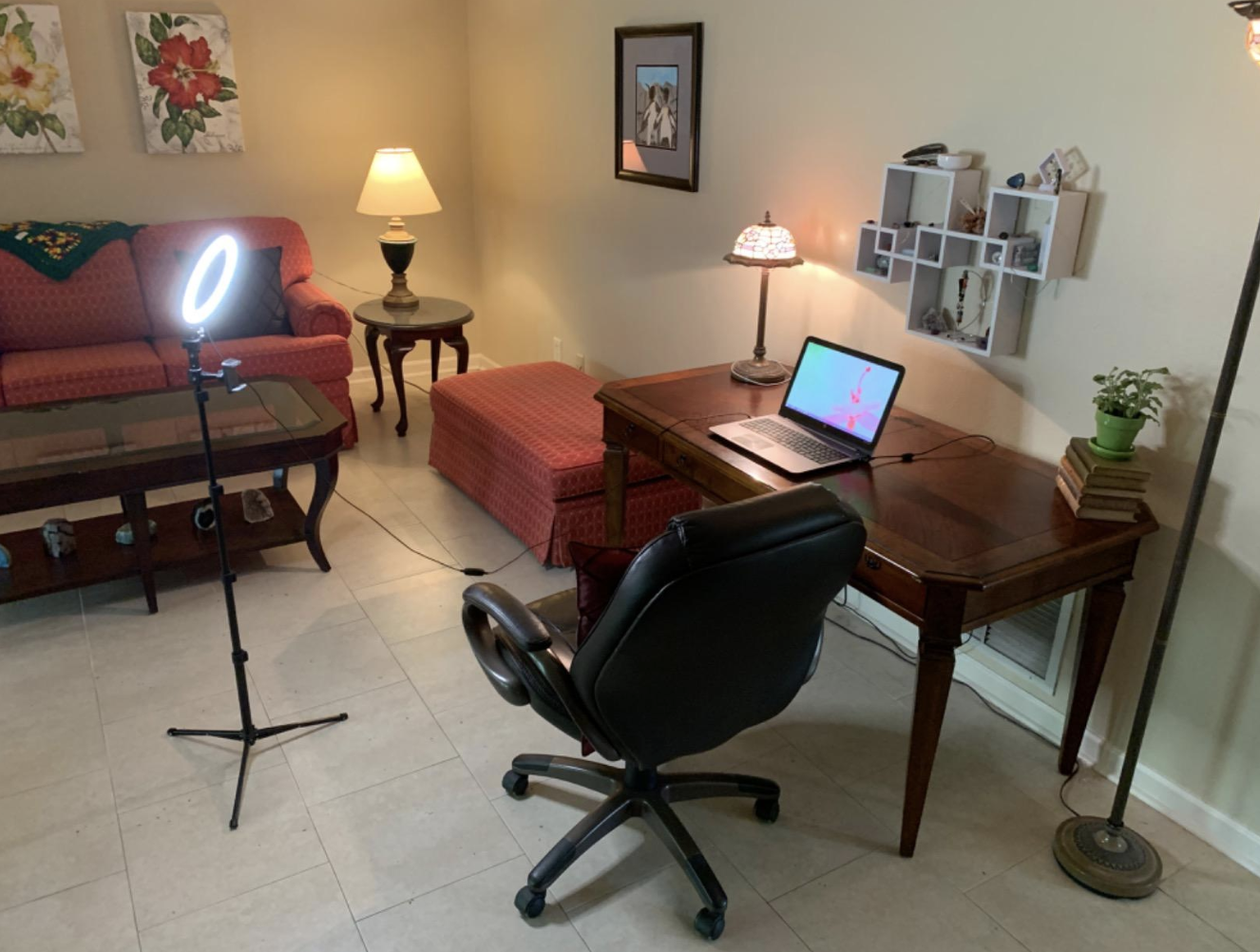 A lit selfie ring on a tripod pointing at a reviewer's desk set up