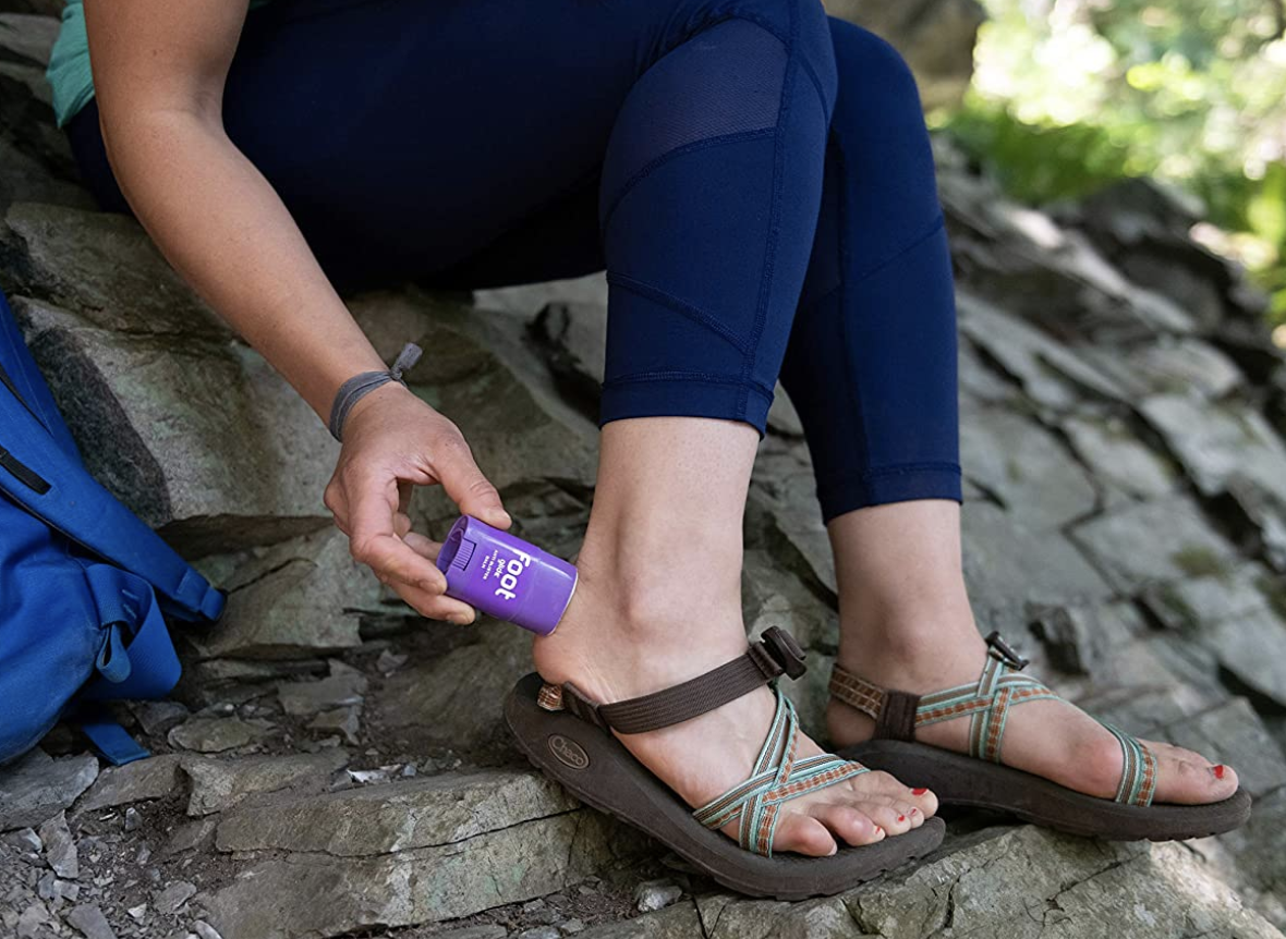 A model applying the deodorant-shaped balm to the back of their heel before putting on strapped sandals