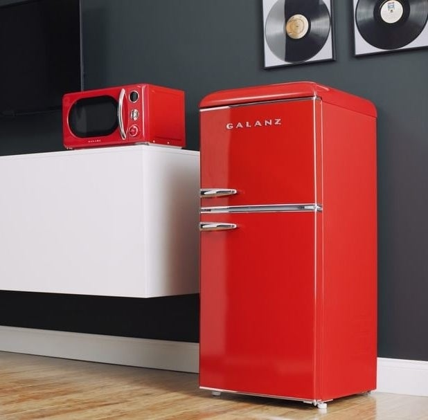 a small, red freezer and fridge with a retro look to it