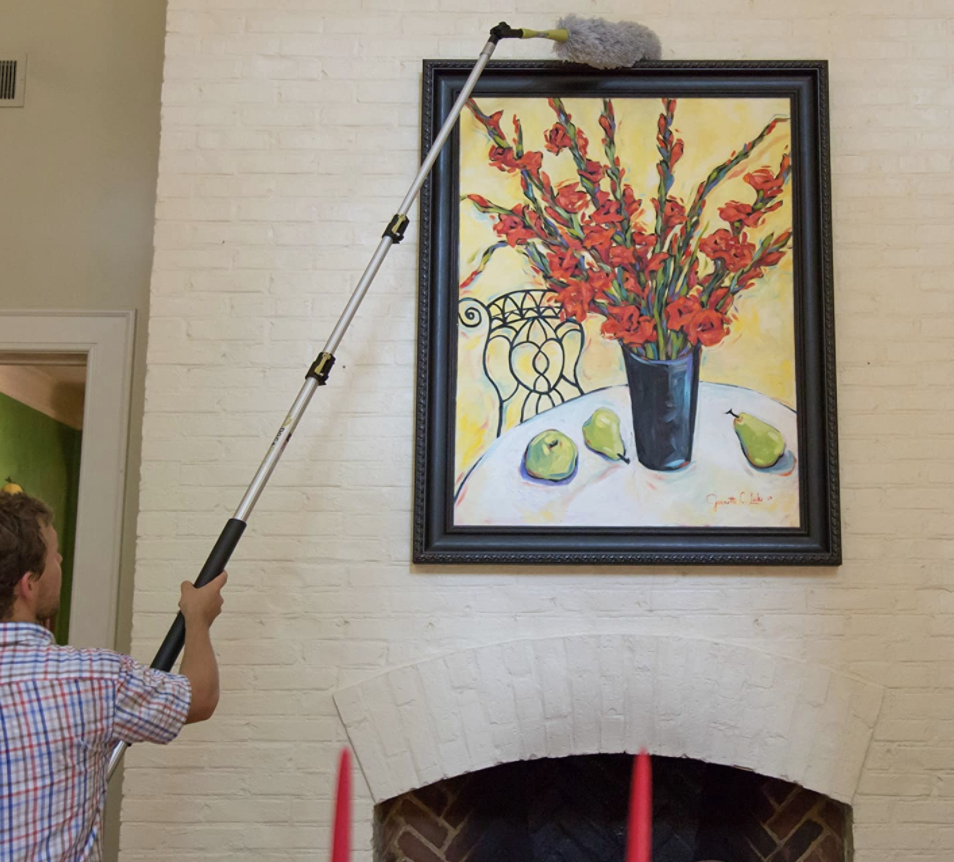 Homeowner uses high-reach dusting kit to wipe away dust from a painting with a vase and fruit over a fireplace