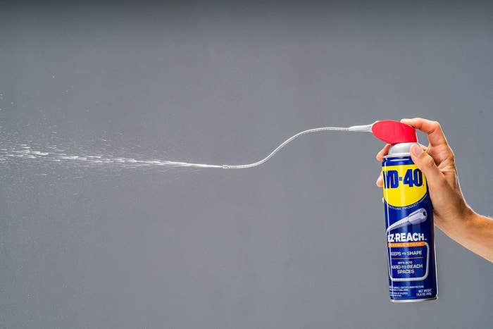 Model's hand holding and spraying blue WD-40 can with red top