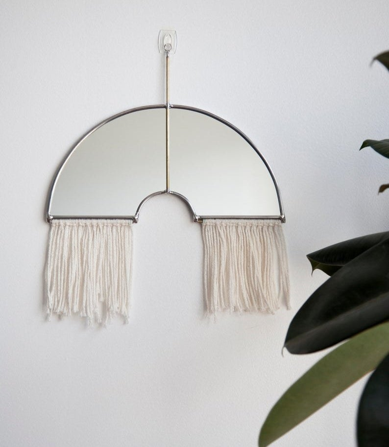 Curved mirror with metal edges and fringe bottom