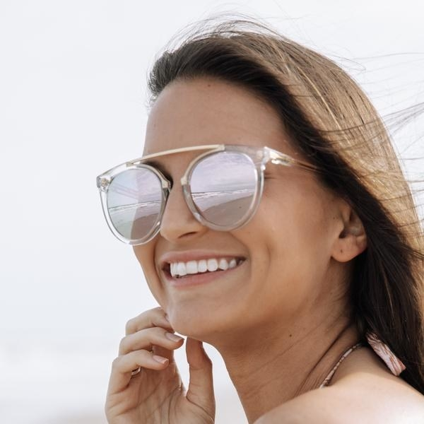 A model wearing clear aviators at the beach. The glasses have no bridge on the nose but are connected at the brow