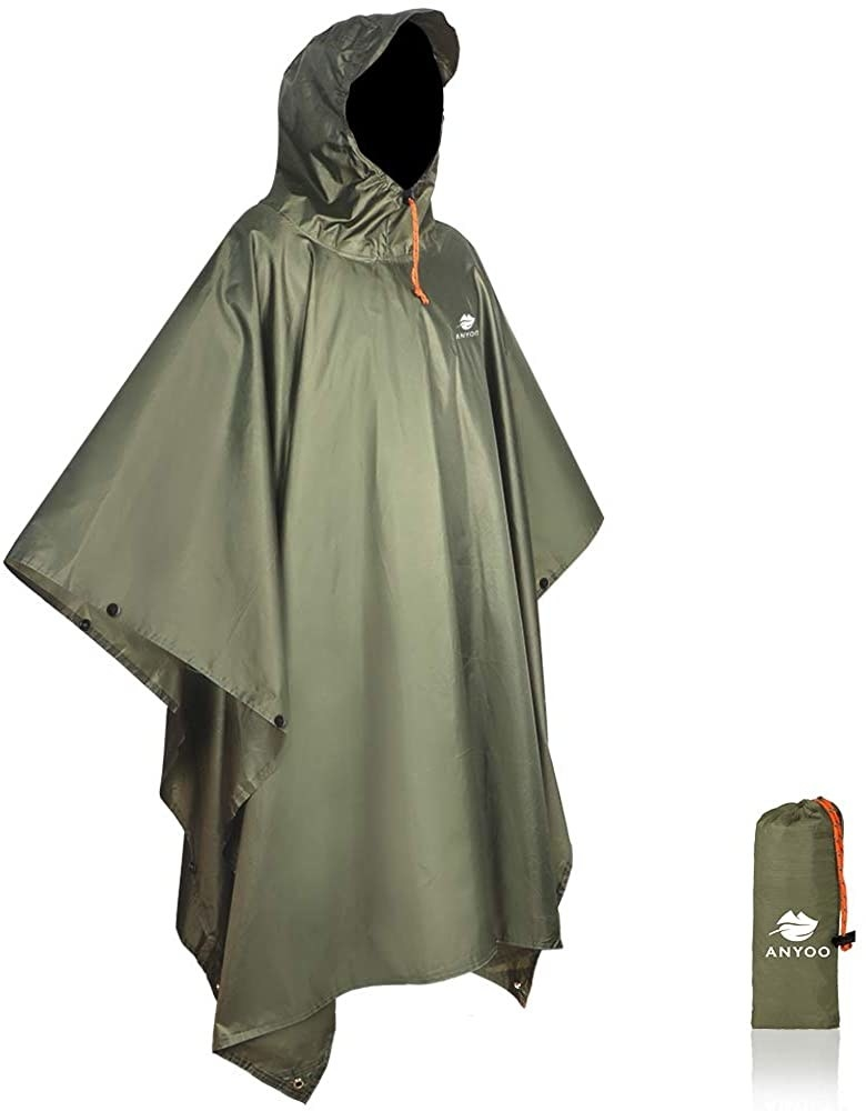 Green poncho on white background with storage bag