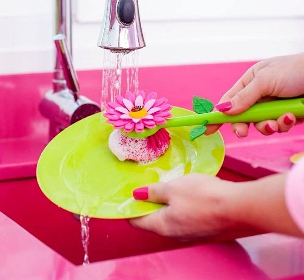 a model using the pink and green flower dish scrubber
