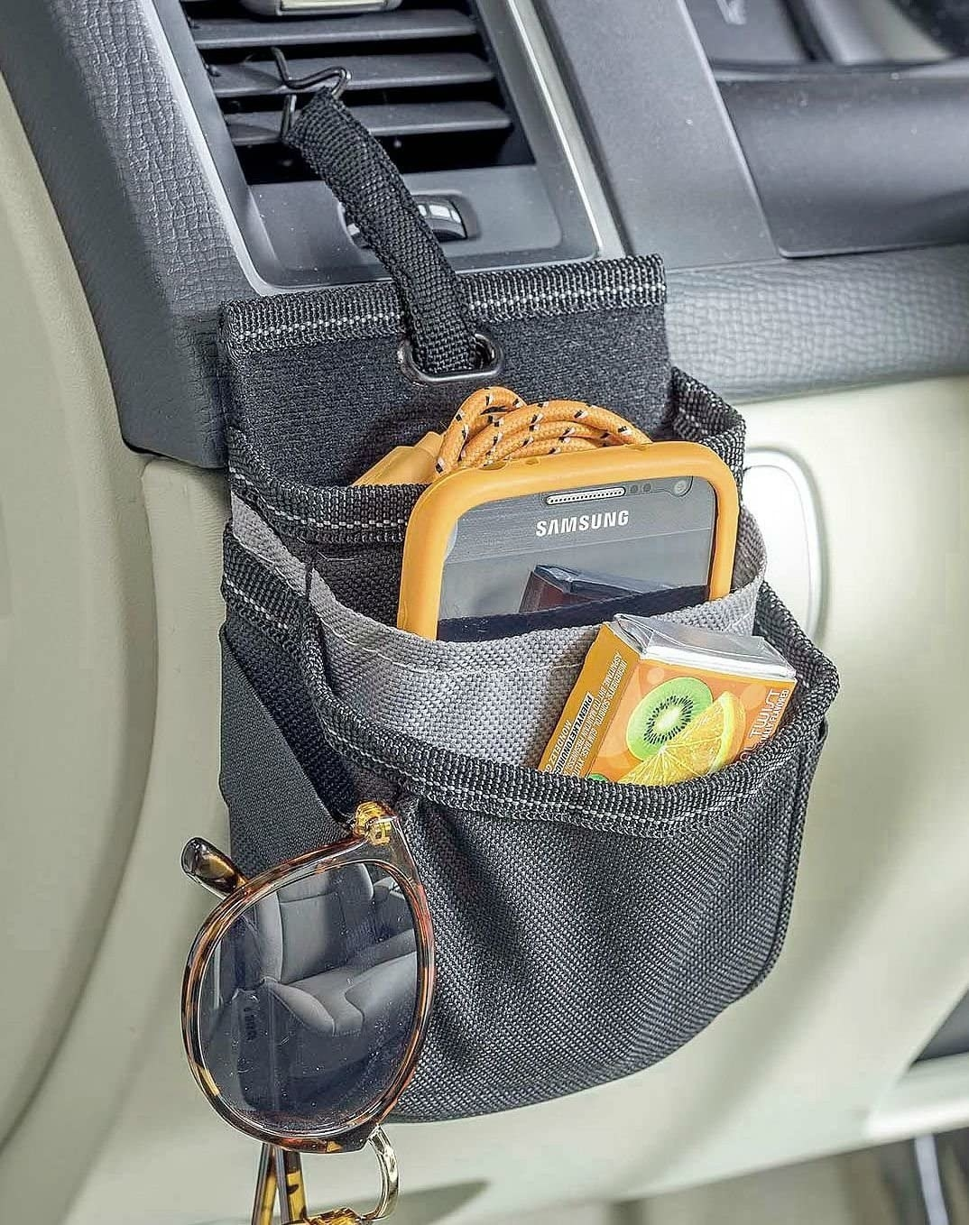 pocketed pouch-like organizer hanging from a car vent