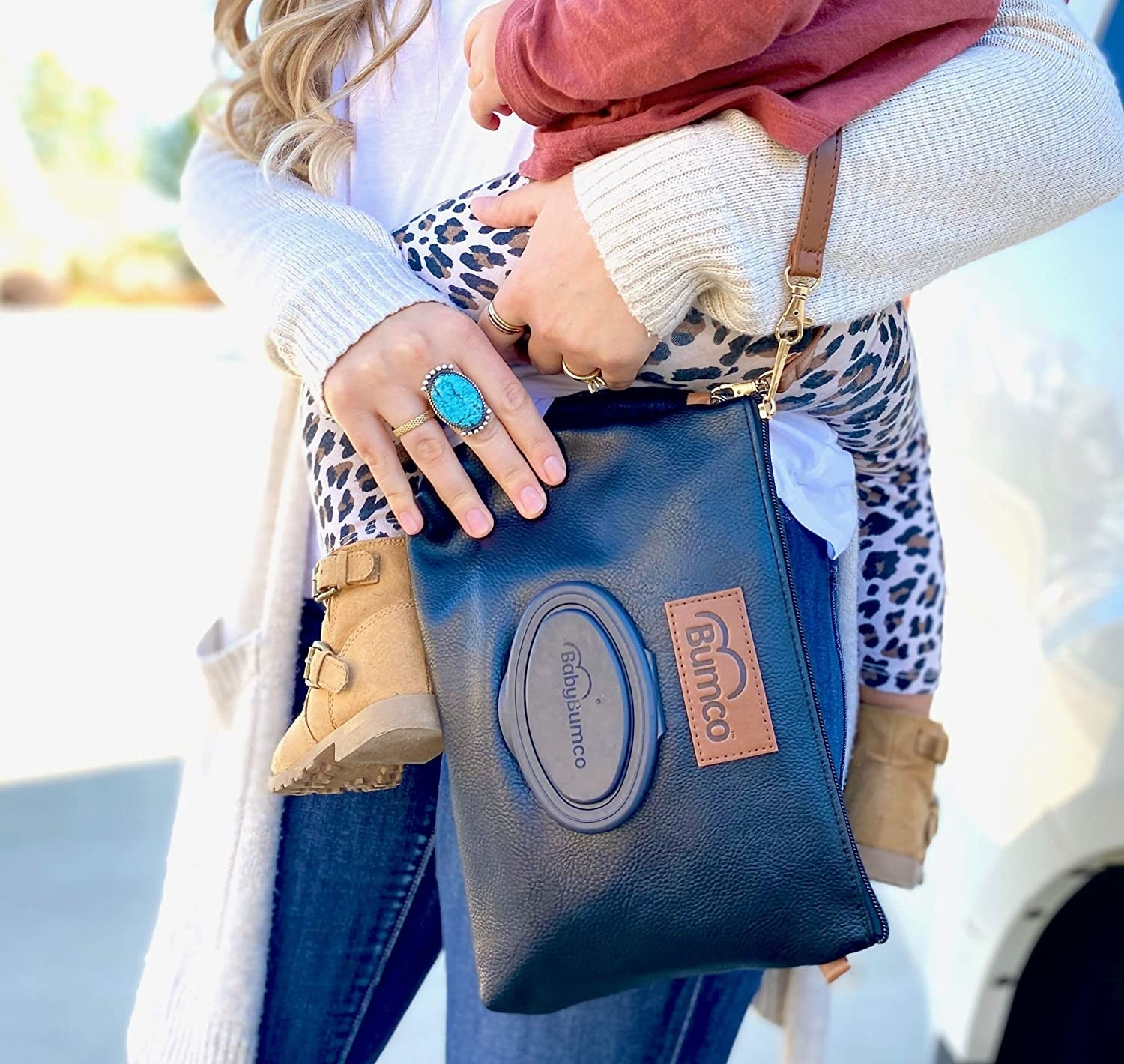 a model carrying a baby and a black diaper wristlet