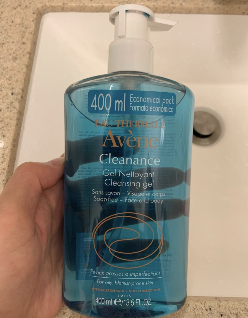 """hand holding clear plastic bottle filled with blue liquid labeled """"Avène Cleanance"""""""