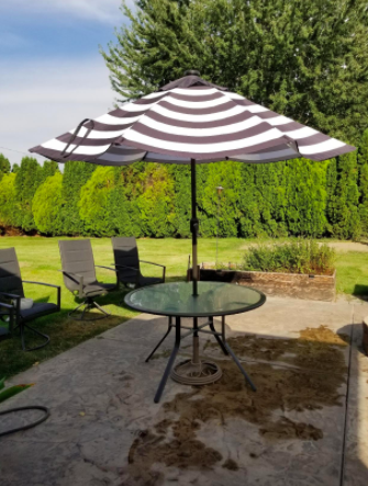 patio with round glass table and a striped umbrella on it