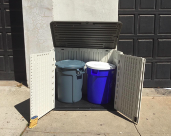 open shed to reveal a trash can and recycling bin