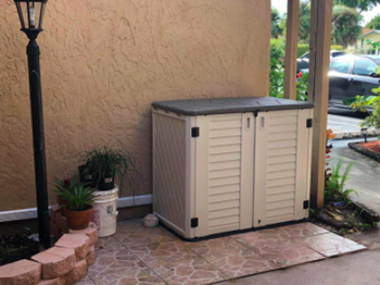 reviewer pic of shed with a lid and to front doors on a patio