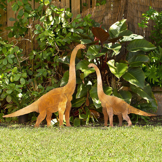 small brontosaurus shaped yard decorations in front of a bush